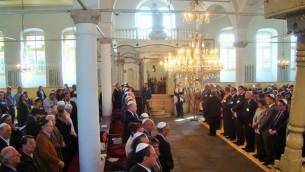 Des membres de la communauté juive, des dignitaires locaux et des diplomates étrangers participent à une cérémonie commémorative à la synagogue Kahal Kadosh Yashan, pour marquer les 70 ans des déportations nazies (Crédit :  Gavin Rabinowitz/JTA)