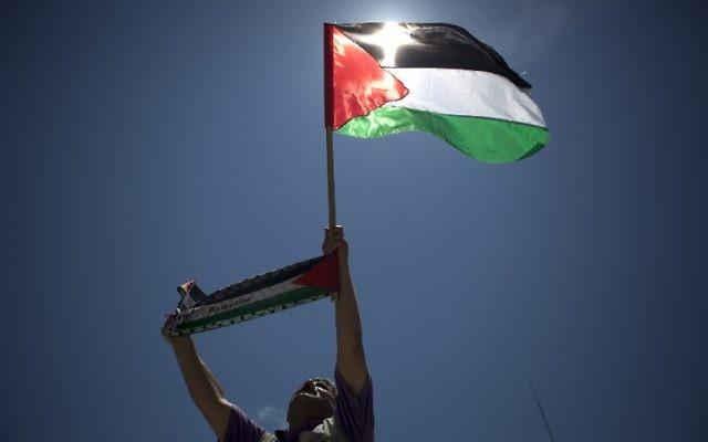 Un Palestinien arborant le drapeau palestinien (Crédit : AFP)