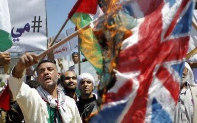 Des Palestiniens brûlent des drapeaux israéliens et britanniques lors du 66ème rassemblement pour la Nakba à Rafah - 14 mai 2014 (Crédit : Said Khatib/AFP)