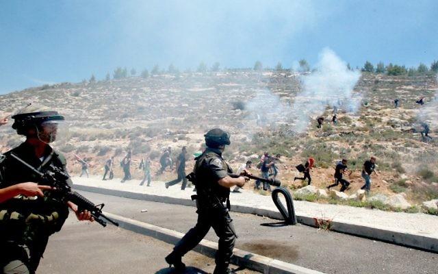 """Gardes-frontières israéliens pendant des affrontements contre des manifestants palestiniens commémorant le 66e anniversaire de la """"Nakba"""" dans le village de Walajah, en Cisjordanie, au sud de Jérusalem, le 15 mai 2014. (Crédit : Musa al-Shaer/AFP)"""
