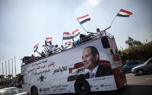 Une affiche de Sissi sur un bus rempli de supporters avec des drapeaux égyptiens en mai 2014 (Crédit : MAHMOUD KHALED/AFP)
