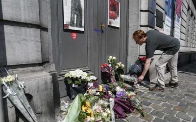 Un homme dépose une gerbe de fleurs devant la porte du musée juif de Bruxelles (Crédit : AFP)