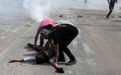 Des Palestiniens aident un ami blessé près de la prison d'Ofer, à Beitunia (Crédit : Abbas Momani/AFP)