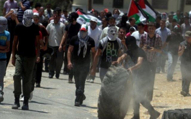 Des Palestiniens jettent des pierres sur les forces de sécurité à Naplouse (Crédit : Issam Rimawi/Flash 90)
