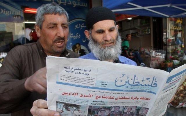 Des Palestiniens qui lisent le journal affilié au Hamas Falastin dans une rue de Hébron (Crédit : Hazem Bader/AFP)