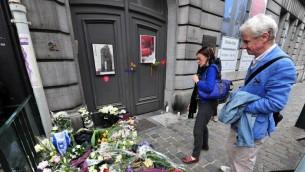 Des gens rendent hommage aux victimes de la fusillade de Bruxelles à l'entrée du Musée juif de la ville, en mai 2014. (Crédit : Georges Gobet/AFP)