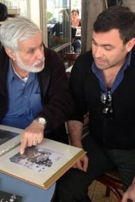 Moshe Zaki montre à son fils Uri un album de famille (Crédit : Renee Zhert Gand)