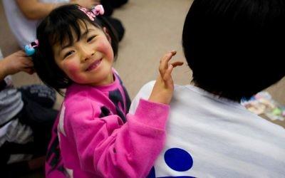 Une enfant japonaise avec un bénévole de IsraAid (Crédit : autorisation IsraAID)