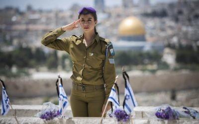 Une soldate israélienne au garde-à-vous pour les soldats tombés à une cérémonie au mont des Oliviers (Crédit : Yonatan Sindel/lash 90)