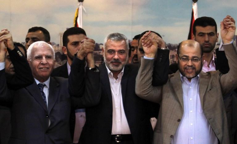 De gauche à droite : le chef de la délégation du Fatah Azzam al-Ahmad, le Premier ministre du Hamas dans la bande de Gaza Ismael Haniyeh et Abu Marzouk, le jour de la signature du pacte de réconciliation entre les deux factions palestiniennes, le 23 avril 2014. (Crédit : Said Khatib/AFP)