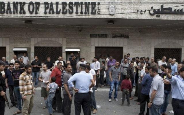 Des hommes palestiniens devant la banque à Gaza (Crédit : AFP/Mohammed Abed)