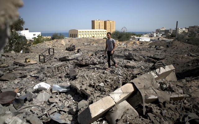 Un Palestinien marchant sur des ruines après un raid israélien (Crédit : AFP/MOHAMMED ABED)
