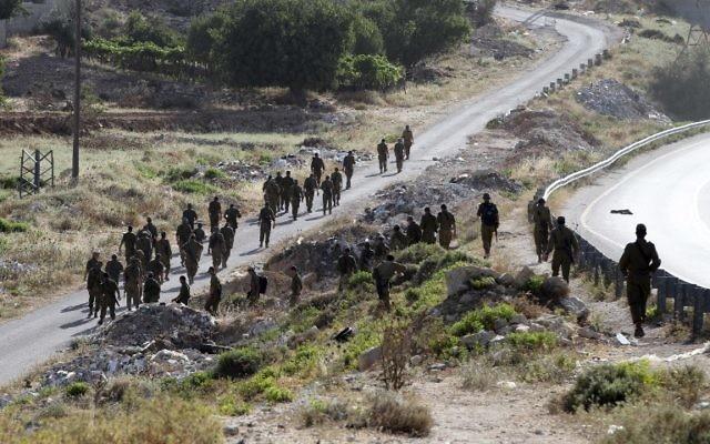 Des soldats israéliens en train de se diriger vers le village de Halhul, près de Hébron (Crédit : AFP/HAZEM BADER)