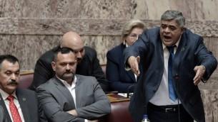 Nikolaos Michaloliakos, (debout) le leader du parti néo nazi Aube dorée durant son procès (Crédit : LOUISA GOULIAMAKI / AFP)