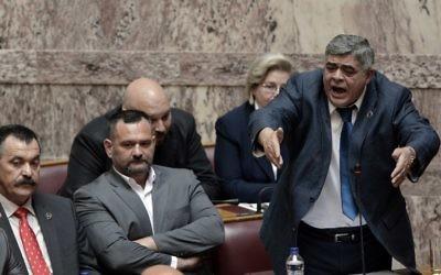 Nikolaos Michaloliakos (debout), le leader du parti néonazi grec Aube dorée pendant son procès, en 2014. (Crédit : AFP/Louisa Gouliamaki)