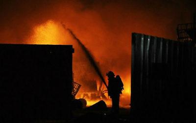 Incendie dans une usine de Sdérot à cause d'une roquette tirée depuis la bande de Gaza (Crédit : AFP/David Buimovitch)