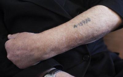 Un survivant de la Shoah montre son bras tatoué par les nazis. Illustration. (Crédit : Yonatan Sindel/Flash90)