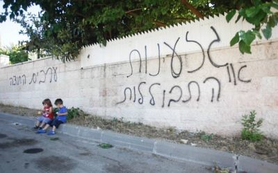 """Des enfants assis près d'un mur où il est inscrit en hébreu : """"racisme ou assimilation"""", """"les Arabes dehors"""" à Abu Ghosh (Crédit : Flash90)"""