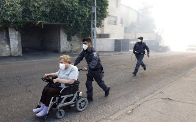 Des pompiers évacuant des résidents après l'incendie qui s'est déclaré à Ein Kerem (Crédit : Yonatan Sindel/FLASH90)