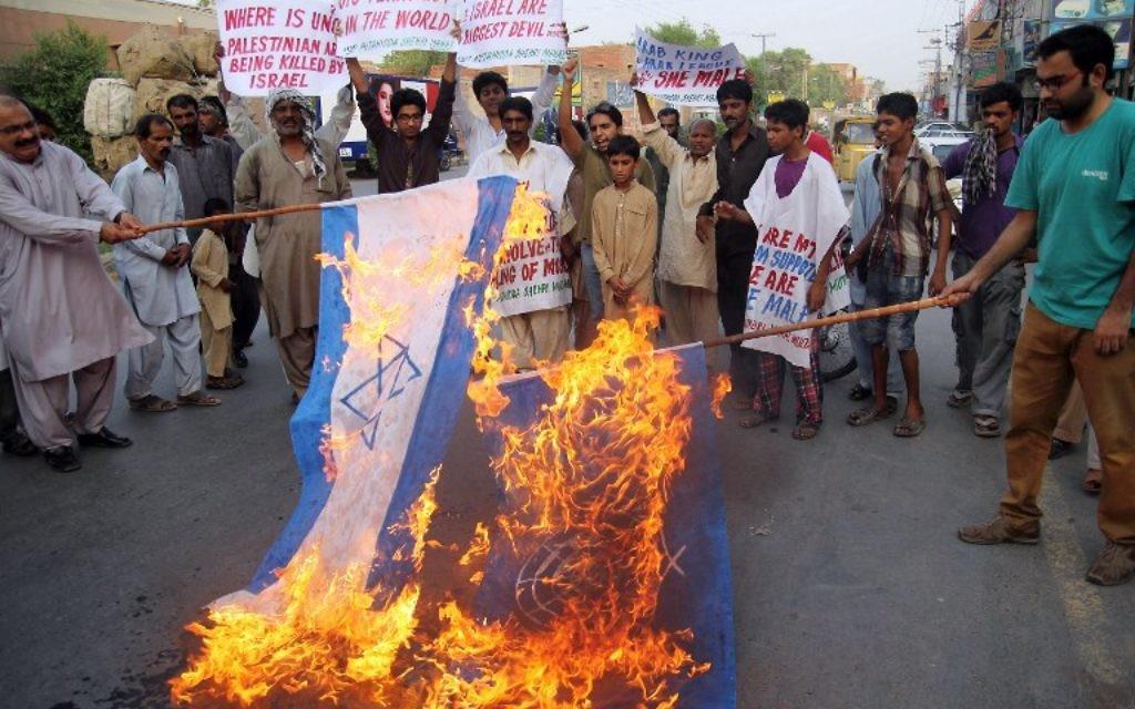 Manifestants pakistanais qui brûlent des drapeaux israéliens et les drapeaux des Nations Unies lors d'une manifestation contre les opérations militaires israéliennes dans la bande de Gaza - Multan, le 22 juillet 2014 (Crédit : AFP PHOTO / SS MIRZA)