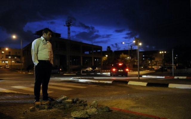 Un civil israélien se tient debout près d'un trou causé par un tir de roquette (Crédit : AFP/David Buimovitch)