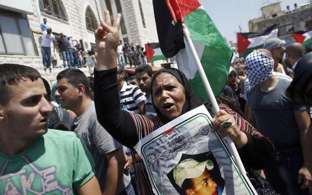 Des manifestants palestiniens escortent le corps du jeune Mohammad Abou Khdeir (Crédit : AFP/Thomas Coex)
