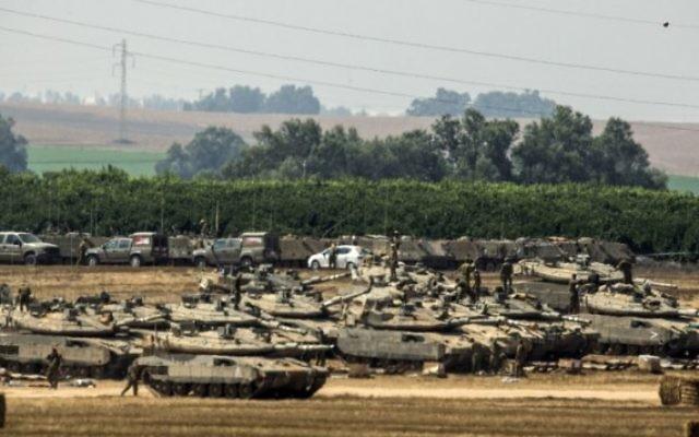 Soldats israéliens situés près de tanks Merkava à proximité de la bande de Gaza (Crédit : AFP/JACK GUEZ)
