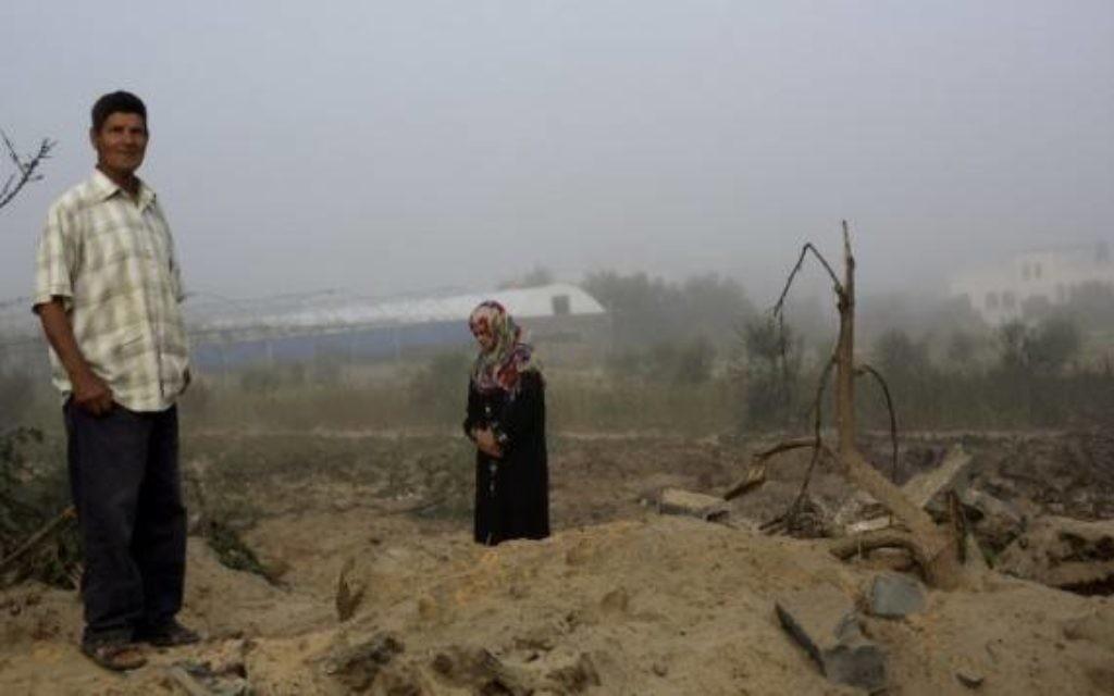Un homme et une femme palestinienne inspectent les lieux après un raid de l'armée israélienne à Khan Younes (Crédit : AFP/MOHAMMED ABED)
