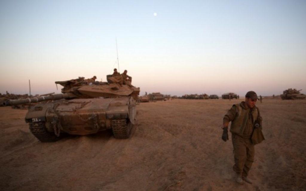 Un soldat israélien et un char déployés près de la frontière avec Gaza (Crédit : Menahem Kahana/AFP)