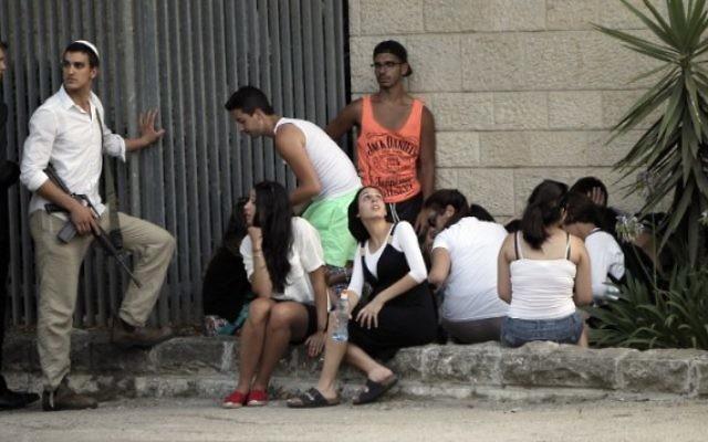 Des Israéliens à l'abri lors d'une sirène retentissant près de Jérusalem (Crédit : AFP: Ahmad Gharabli)