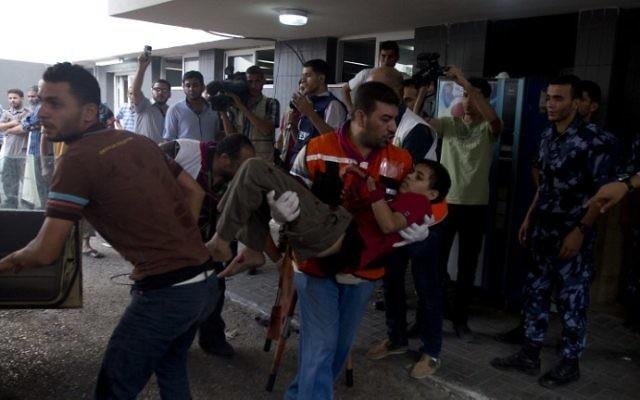 Un garçon palestinien blessé emmené à l'hôpital de Shifa (Crédit : Mahmud Hams/AFP)