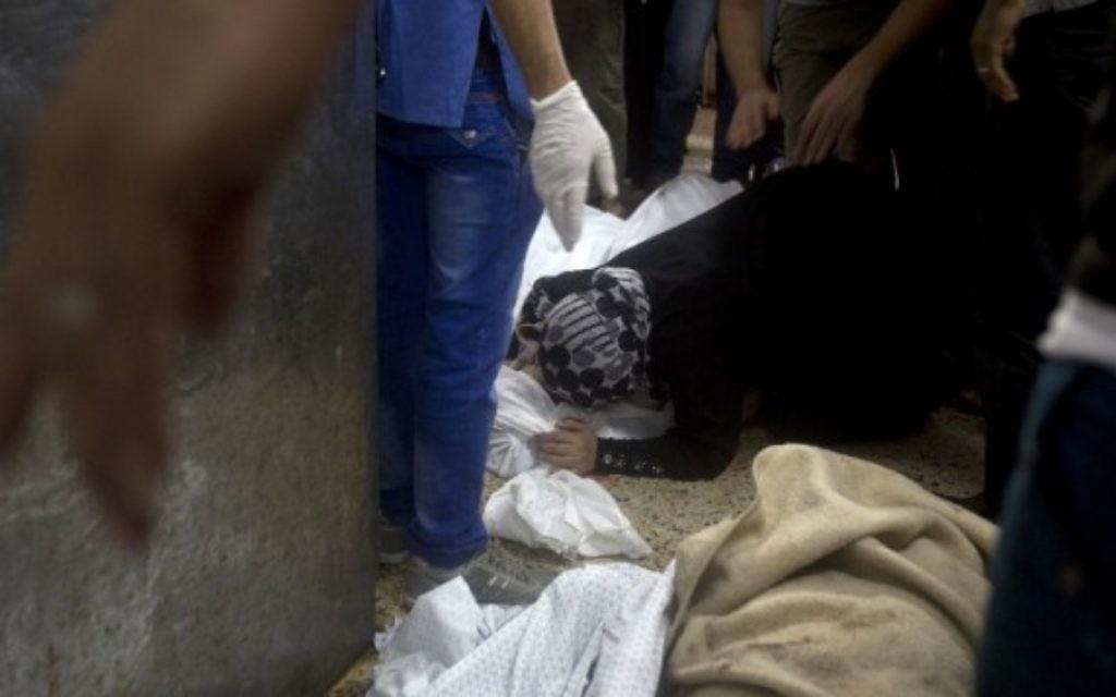 Une femme pleurant le corps d'un mort à l'hopital de Shifa (Crédit : AFP/MAHMUD HAMS)