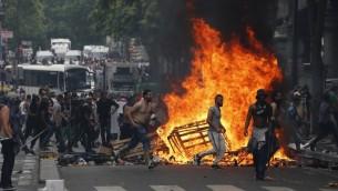 Des Français en train de courir devant un feu à Barbès-Rochechouart - 19 juillet 2014 (Crédit : AFP/ FRANCOIS GUILLOT)