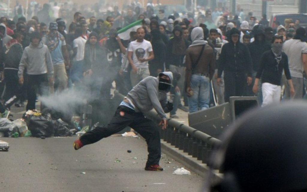 Un émeutier jette des pierres sur la police à Sarcelles, près de la synagogue de la ville, pendant une manifestation anti-Israël pendant l'opération Bordure protectrice, le 20 juillet 2014. (Crédit : AFP/Pierre Andrieu)
