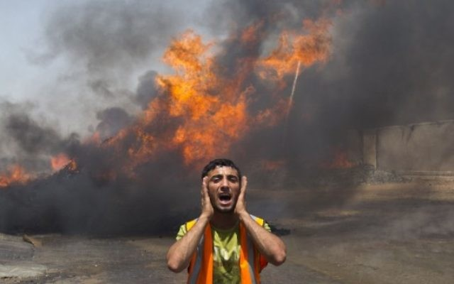 Un pompier palestinien tente d'éteindre le feu provoqué par une frappe aérienne israélienne (Crédit : AFP/Mahmud Hams)