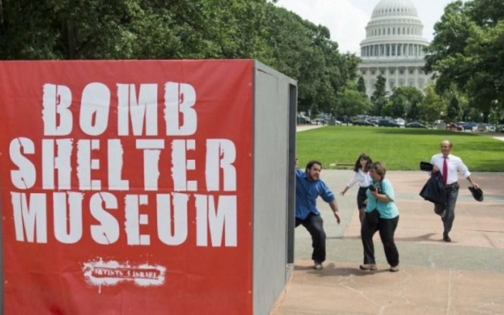 """Les gens courent vers une maquette d'un abri anti-bombes lors d'une attaque simulée par les roquettes du Hamas dans le cadre d'une exposition d'art multimédia appelée """"Le Musée Bomb Shelter"""" qui s'inspire des abris en Israël, près du Capitole des États-Unis à Washington, le 22 Juillet 2014. (Crédit : AFP / Saul Loeb)"""