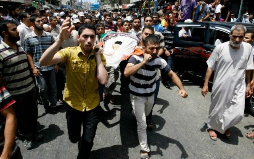 Des Palestiniens transportent le corps d'un terroriste du Hamas (Crédit :  Abed Rahim Khatib/Flash90)