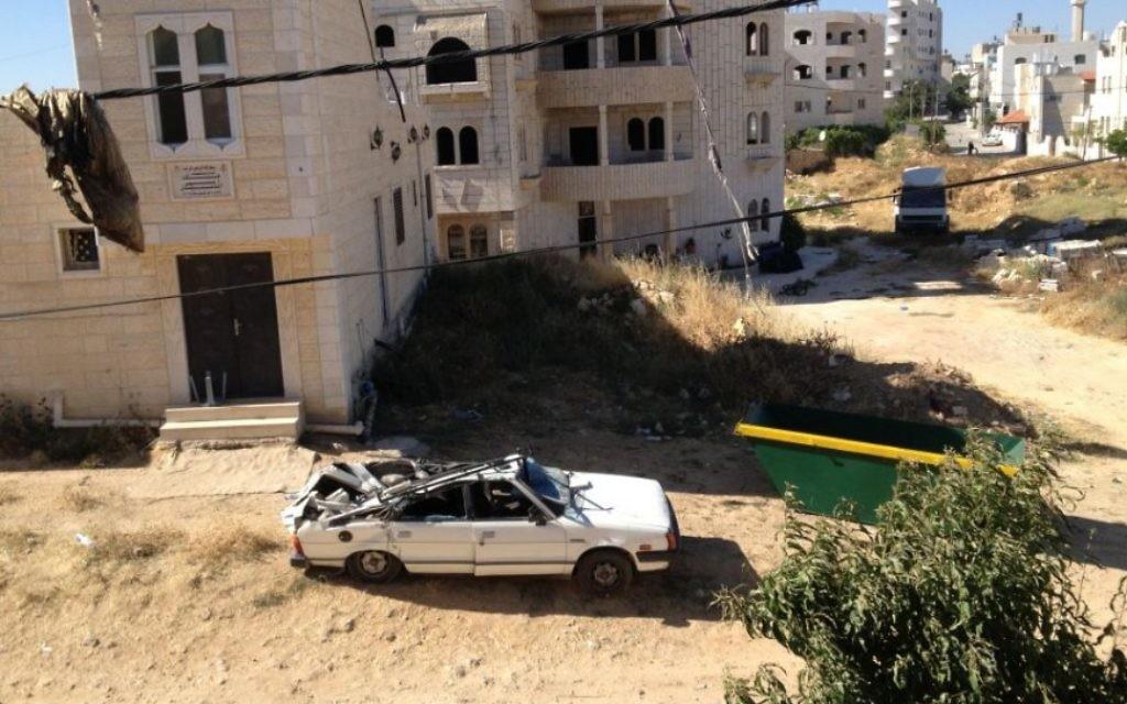 Une voiture détruite à cause des pierres de la maison qui sont tombées à l'extérieur (Crédit : Elhanan Miller/Times of Israel)