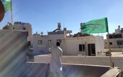 Le drapeau du Hamas qui flotte au-dessus d'une maison (Crédit : Elhanan Miller/Times of Israel)