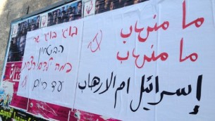 """Pancartes en hébreu et en arabe où l'on peut lire : """"Israël est la source du terrorisme"""" et « ministre de la Défense Boogie, combien d'enfants avez-vous tué jusqu'à présent » (Crédit : Elhanan Miller / Times of Israël)"""
