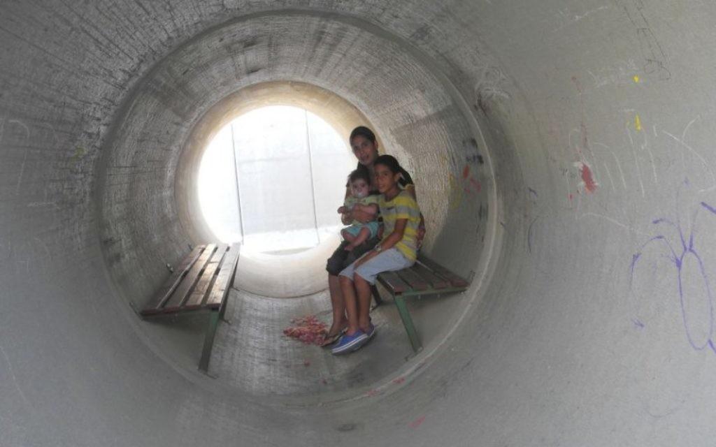 Une famille israélienne se réfugie dans un abri anti-bombes fait d'une canalisation en béton aménagée pendant la guerre de Gaza en 2014. (Melanie Lidman/Times of Israel)
