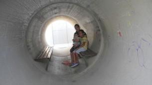 Devorah Israeli, de Nitzan, avec Idan, 8 ans et Ron, 6 mois, dans la canalisation d'eaux usées d'un abri anti-bombe à côté de sa maison, dont les habitants se plaignent que ce n'est pas une protection suffisante (Crédit : Melanie Lidman / Times of Israël)