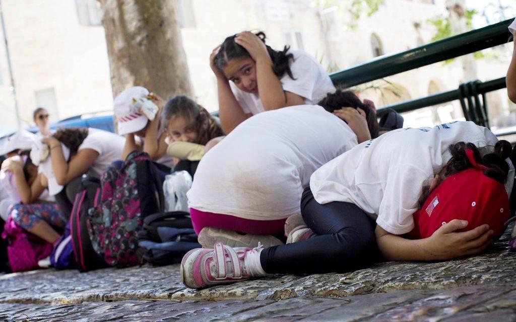 Un groupe d'écoliers se protègent dans le quartier juif de Jérusalem alors que les sirènes retentissent dans tout Israël dans le cadre d'un exercice de simulation du commandement de la Défense d'un attentat à la bombe, le 27 mai 2013 (Crédit : Sarah Schuman / Flash90)
