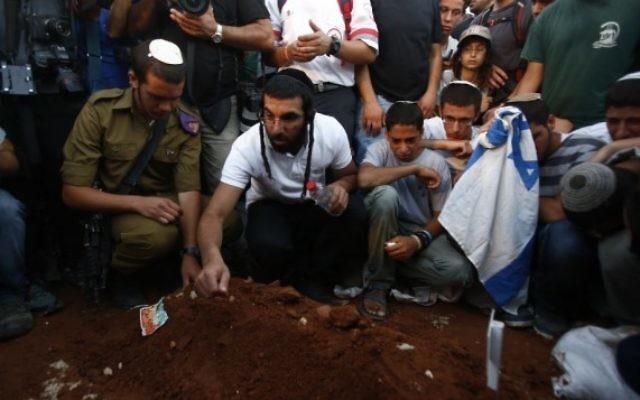 Des hommes posent des pierres sur tas de terre qui ensevelit les adolescents assassinés (Crédit : Yonatan Sindel/Flash 90)
