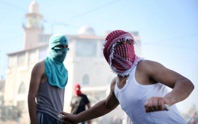 Des Arabes israéliens à Jérusalem-Est lançant des pierres sur la police (Crédit : Hadas Parushi/Flash 90)