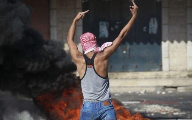 Un activiste palestinien lance des pierres à la police israélienne à Shuafat - 2 juillet 2014 (Crédit : Hadas Parush/Flash90)