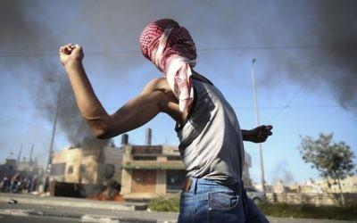 Un Palestinien lançant des pierres sur les autorités israéliennes (Crédit : Hadas Parush/Flash 90)