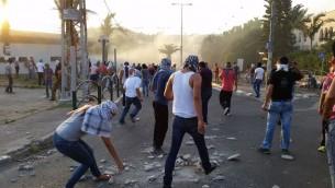 Des jeunes Palestiniens lancent des pierres sur les polices (Crédit : Flash 90)