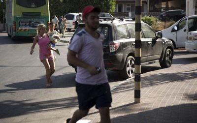 Des habitants de Sderot courent pour s'abriter des roquettes lancées depuis Gaza (Crédit : Hadas Parush/Flash 90)