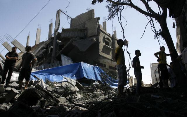 Palestiniens marchant parmi les décombres d'une maison détruite suite à un tir de missile israélien, à Rafah le 14 juillet, 2014 (Crédit : Abed Rahim Khatib/Flash90)